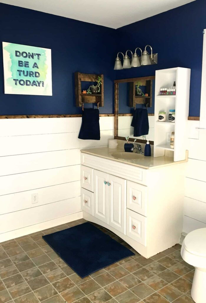 Navy and white bathroom makeover with shiplap and lots of DIY shelves!