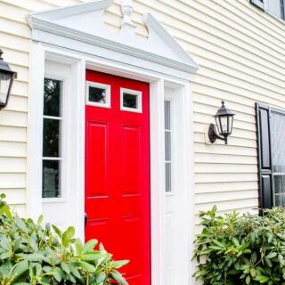 after yellow siding house with red painted door_
