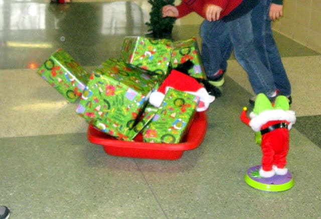 A blurry  photo of a kids obstacle game based  on the  Grinch Who Stole Christmas. The photo shows wrapped presents being pulled in a sled  indoors.