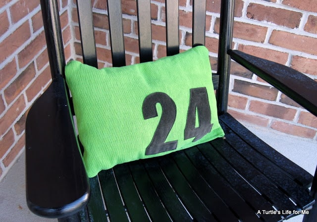 A  green pillow with the number 24 in black sits on a black chair on a front porch.