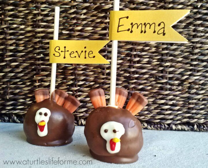 2 upside down chocolate covered turkey cake pops on a piece of cloth. The feathers are made from candy corn and the cake pop sticks have flags with guests names on them so they can be used as thanksgiving place cards.