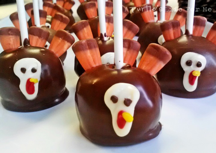A batch of upside down chocolate covered turkey cake pops for thanksgiving sit on a white counter. the feathers are made from candy corn and the faces from candy melts.