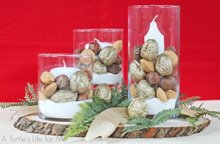 White votive candles in glass flower vases are surrounded by natural and gold spray painted nuts and grouped with green leaves to make a nice Christmas  table centerpiece