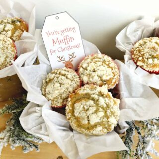 "2 muffin gift baskets packaged with tissue paper and a tag that says, ""you're getting muffin for Christmas"""