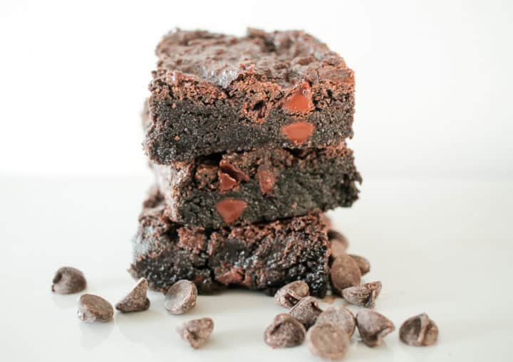 Double Chocolate Fudge Brownies  are the Ultimate Fudge Brownie! Fudge brownies with chocolate chips are pictured stacked 3 tall on a white plate against a white background. Chocolate chips are scattered  in the foreground.