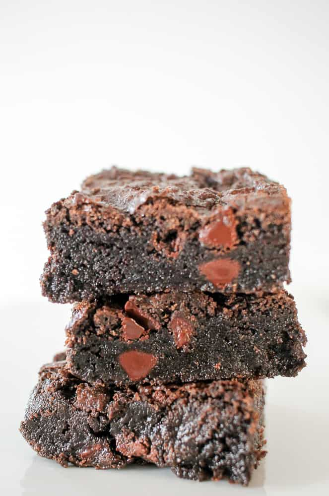 Double Chocolate Fudge Brownies  are the Ultimate Fudge Brownie! Fudge brownies with chocolate chips are pictured stacked 3 tall on a white plate against a white background.