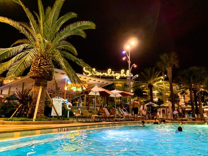 hotel pool and restaurant at night time with a palm tree