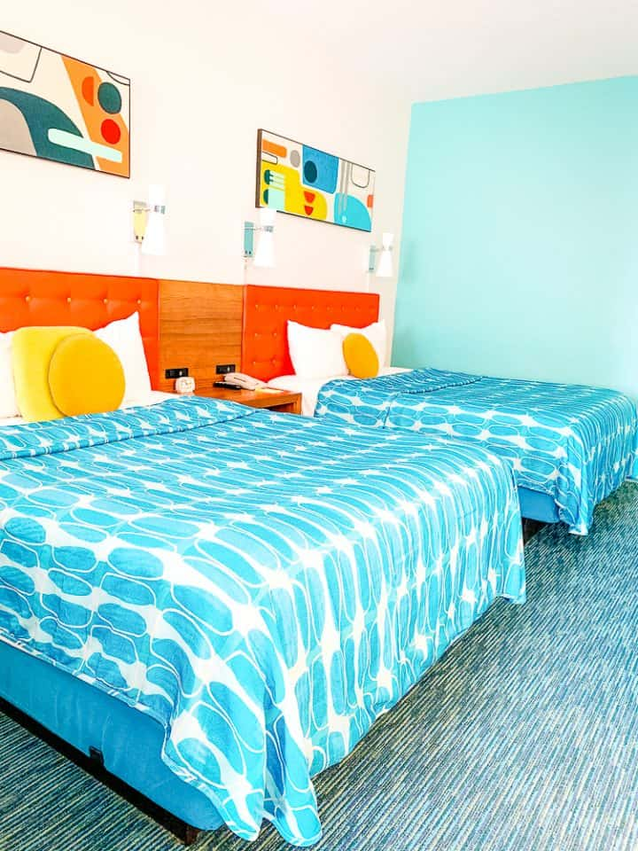 2 queen beds with turquoise and orange color scheme