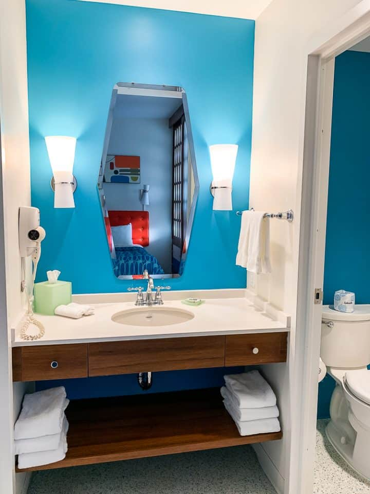 bathroom vanity with blue walls and water closet to the right