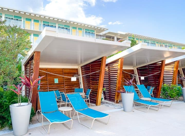 wood cabanas with turquoise lounge chairs at hotel pool