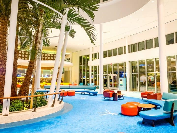 lobby at Cabana Bay Beach Resort with blue carpet, retro furniture and a large palm tree