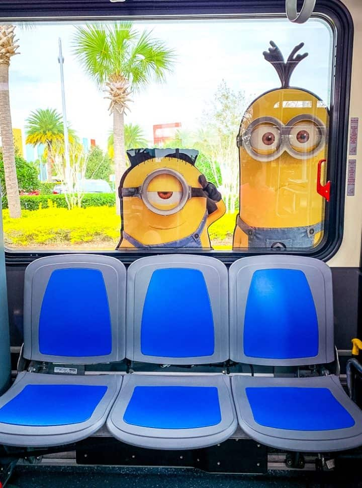 bus seats with minion on the window and palm trees outside