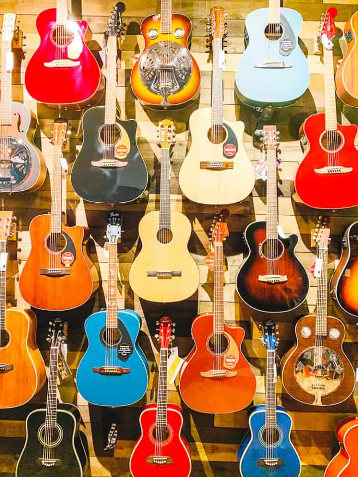 wall of colorful acoustic guitars at The Guitar Shop USA