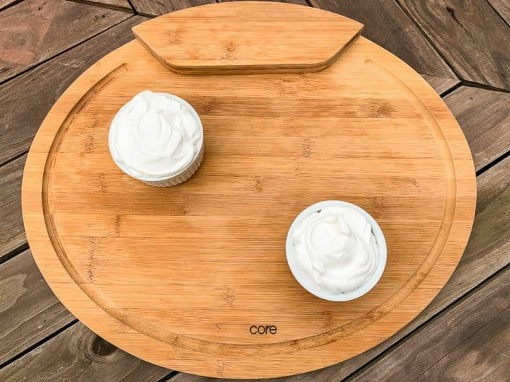 cutting board with 2 small cups of whipped cream