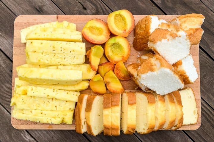 cutting board with pineapple spears, peach halves, angel food cake and pound cake slices to grill