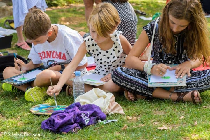 candid action shot of kids painting in grass