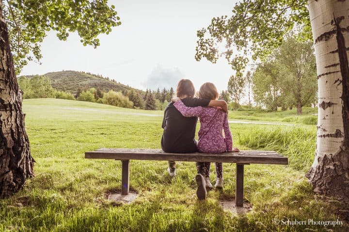 photo of the backs of two kids sitting on a bench in a field