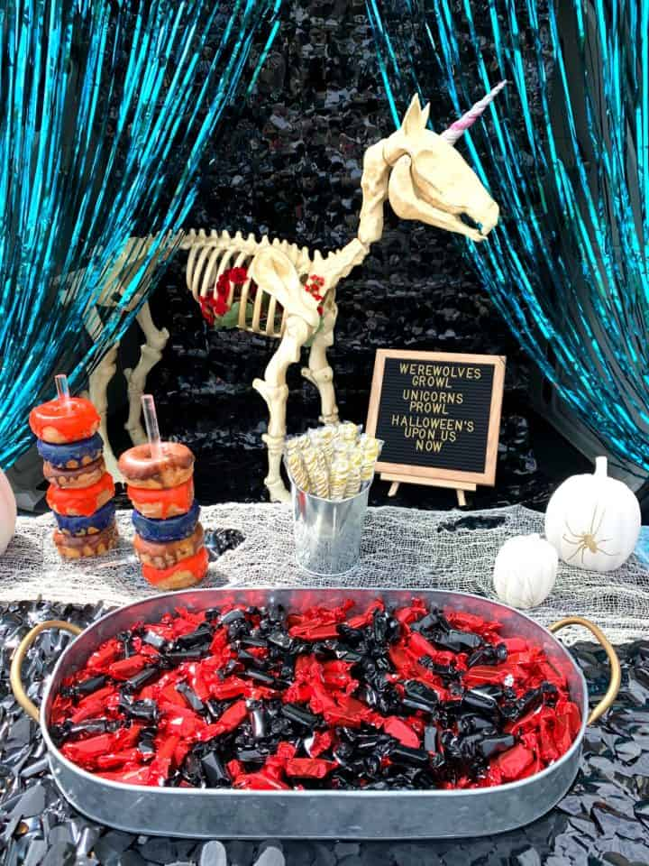 tray of red and black candy with a unicorn in the background for trunk or treat