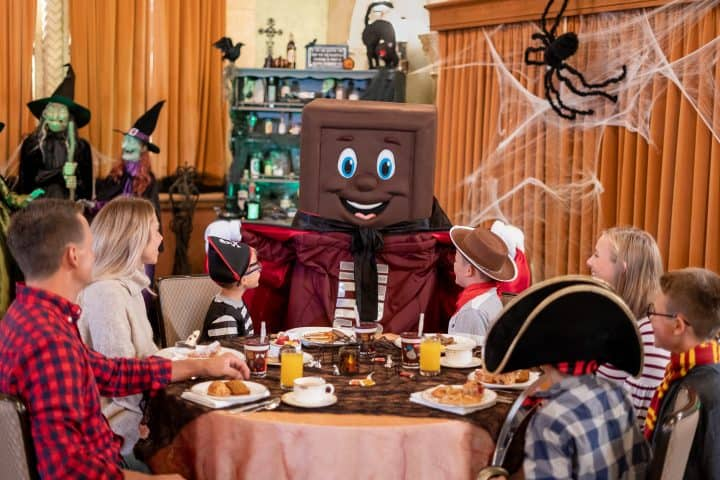 The Hershey Bar costume character talking to a family at a breakfast table