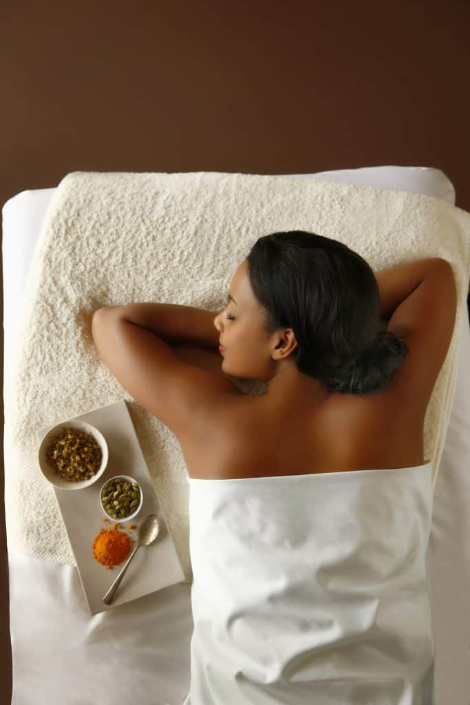 lady laying face down on a bed at a spa with sugar scrubs beside her