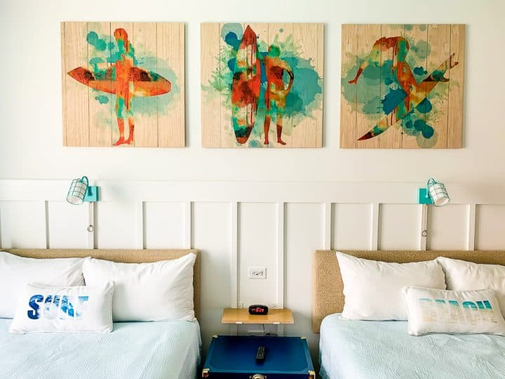 2 queen beds with surf pictures above them
