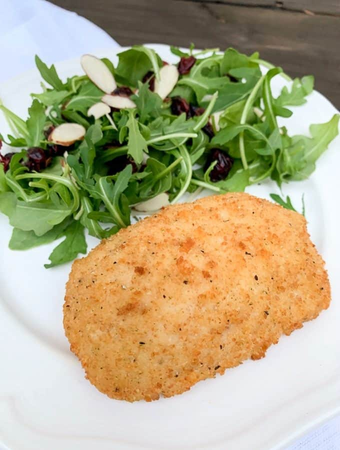 white plate with chicken cordon blue and a salad with cranberries and almond slices