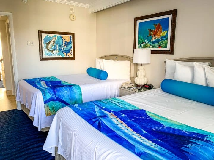 two queen beds in hotel room with tropical decor