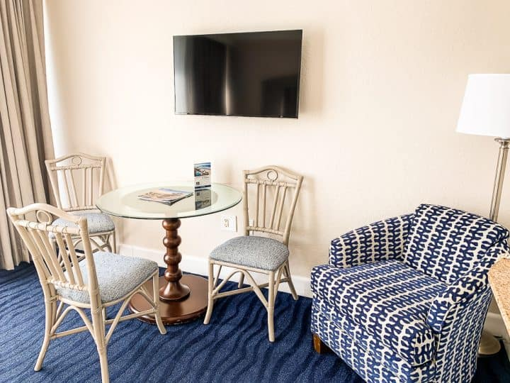 table and chairs in hotel room with tv above it