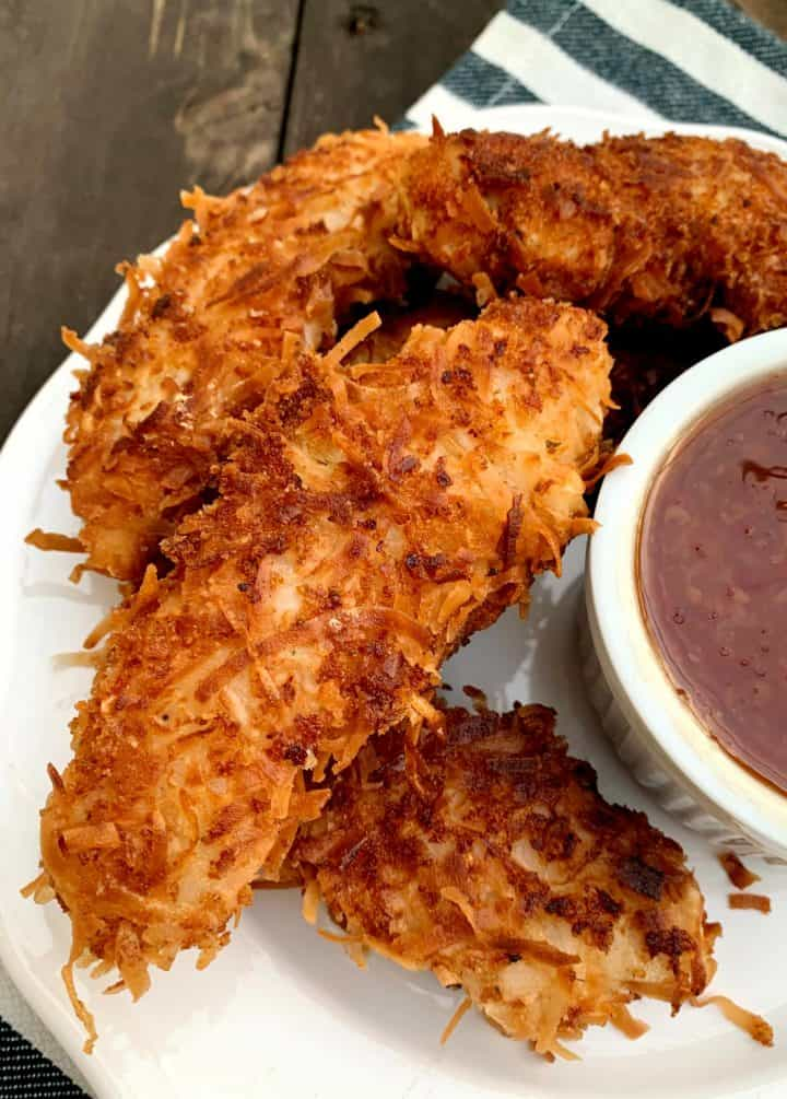 coconut chicken tenders on a white plate