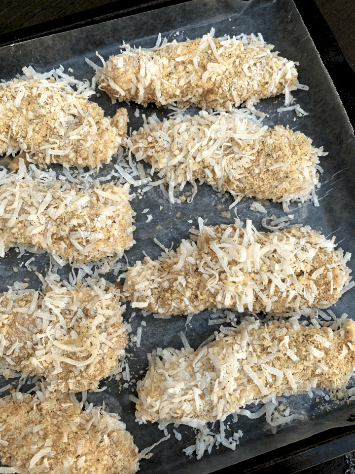 raw chicken tenders covered in shredded coconut and panko bread crumbs
