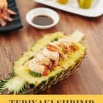 A Pinterest Pin with an image of a pineapple boat with grilled shrimp on a table. The text saysTeriyaki Shrimp Pineapple Boats.