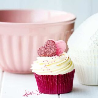 an image of a homemade valentines themed cupcake and cupcake liners and a mixing bowl on a white wooden table