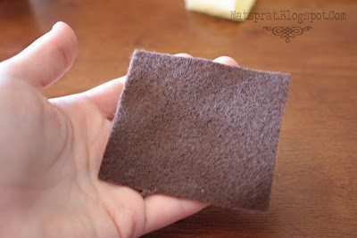 A hand holding a small square of grey felt