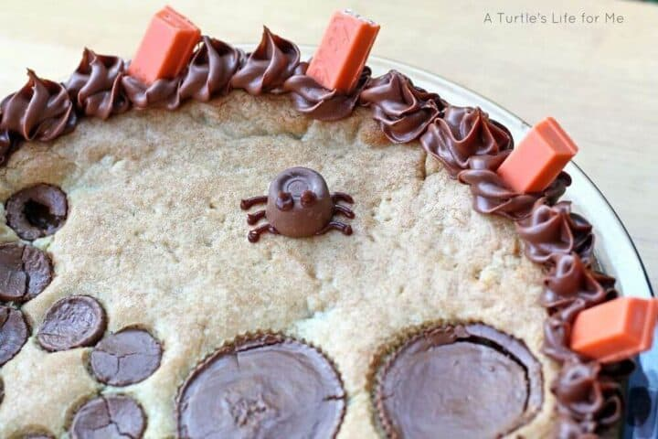 A detailed photograph of a spider made from a Rolo chocolate candy and frosting sitting atop a cookie pie that is Halloween themed