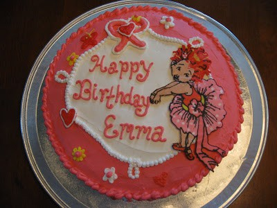 A photograph of a pink and white fancy nancy cake made using icing sheet transfers to put a picture on a cake