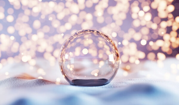 An empty glass Christmas ball ornament on snow with bokeh white background