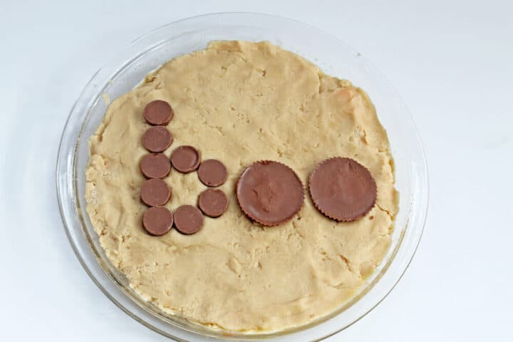 """A process shot of a cookie pie being made, showing the cookie pressed into a baking dish and the word """"boo"""" spelled out with rolo candies and 2 chocolate peanut butter cups"""