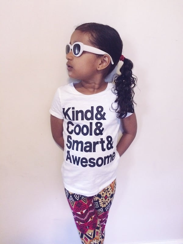 A young girl wearing white sunglasses and a white tshirt with the text  Kind & Cool & Smart & Awesome. She is  looking to the side and standing against a white wall.