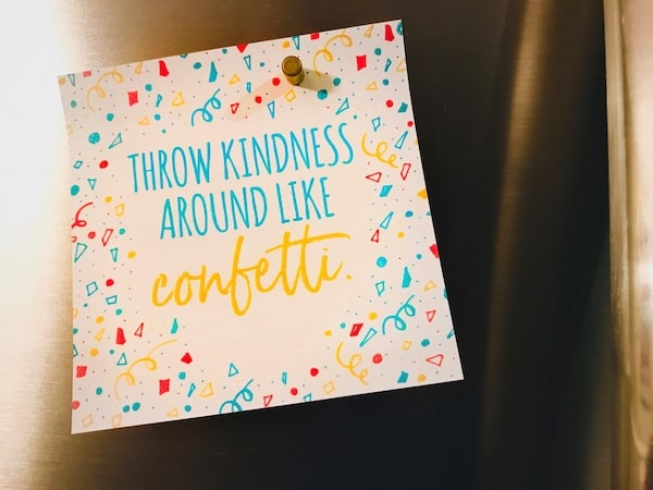"A colorful card displayed on a stainless steel refrigerator. The text says, ""Throw Kindness Around Like Confetti"" and the card's border  has blue and red and yellow confetti drawings."