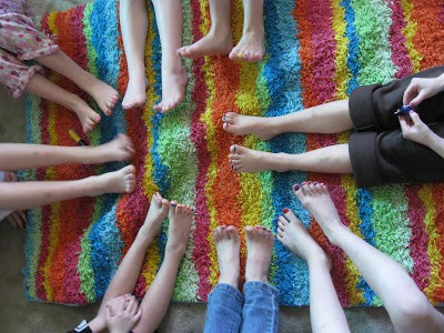 A birds eye photo of young girls' legs and feet together in a circle. Their toenails are painted different colors.