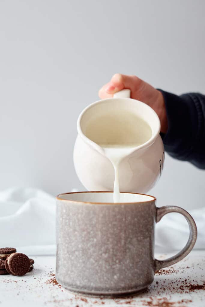 A hand is seen pouring hot milk from a white milk jug into a mug. The mug sits on a white table with mini Oreos and hot chocolate powder strewn on the table.