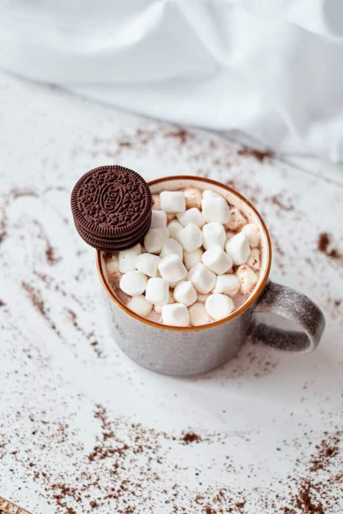 A mug of hot chocolate made using a hot cocoa bomb. Pictured is a mug of hot chocolate topped with mini marshmallows and a stack of mini Oreos against an isolated white background.