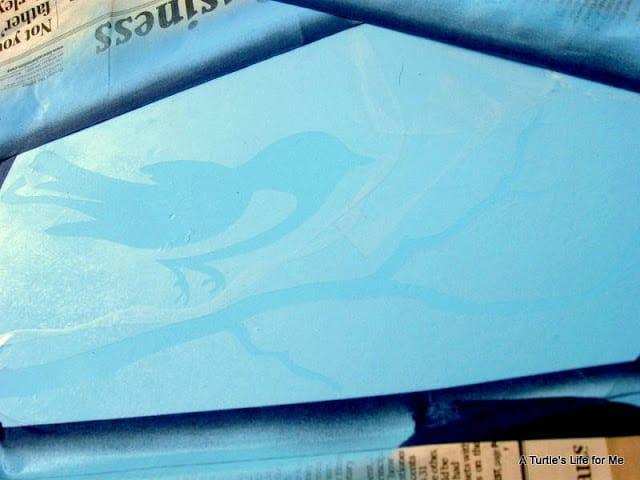A bird on a branch shaped stencil being made to use on the top of an old wooden desk that's painted robin's egg blue