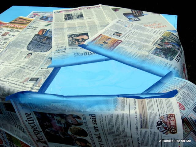 Newspaper covers part of a desktop in preparation for spray painting a stencil on the desk