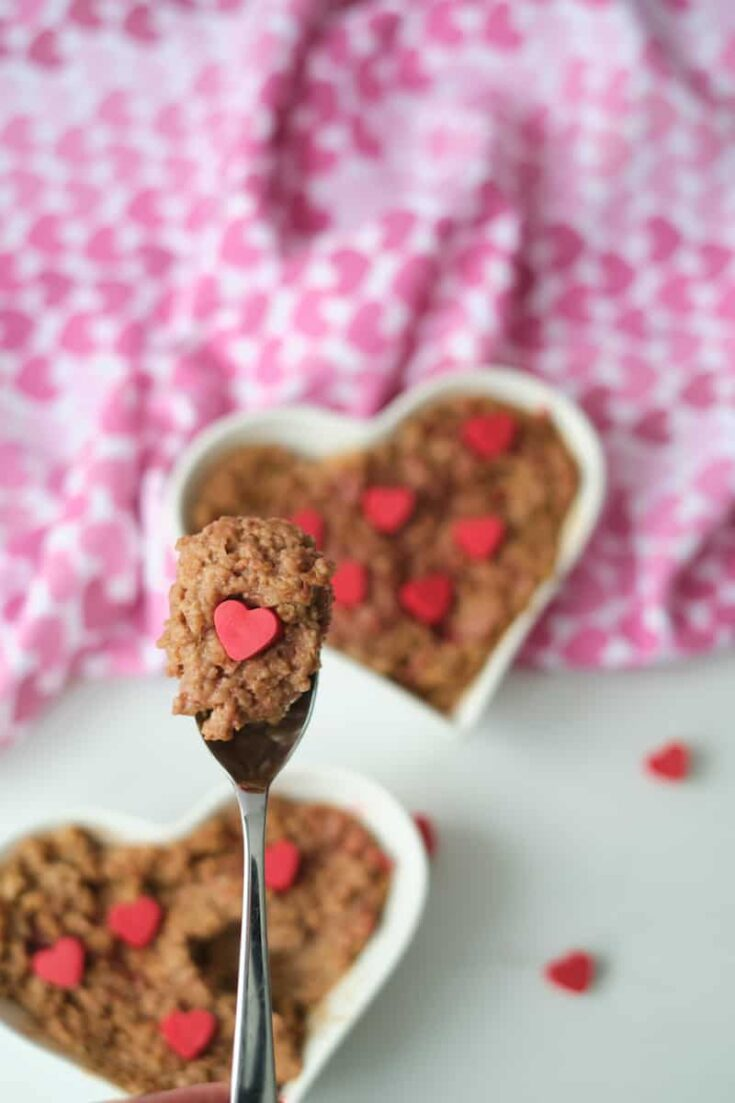 A spoon filled with a mouthful of chocolate oatmeal and a handmade melting wafer heart in the foreground. Chocolate oatmeal in a heart shaped bowl and garnished with red candy hearts in the background.
